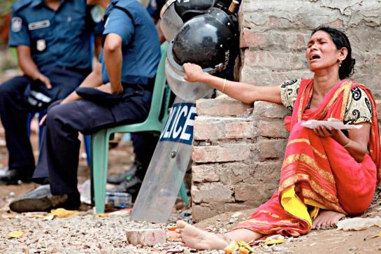 Une mère (dans sa main, elle tient des photos de son fils disparu au Rana Plaza)